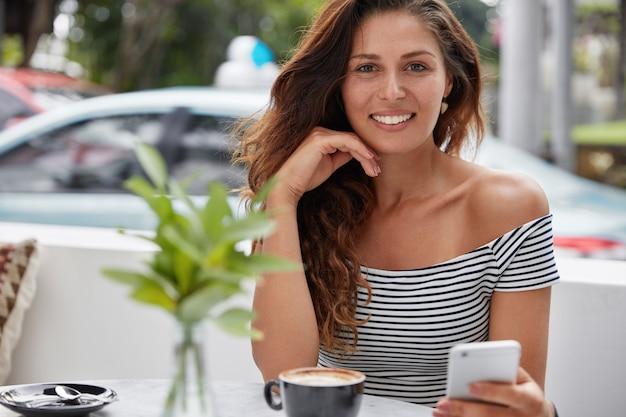 Glückliche schöne junge frau mit charmantem warmem lächeln, installiert neue anwendung auf modernem smartphone Kostenlose Fotos