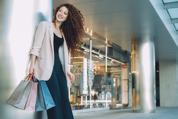 Glückliche schöne junge rothaarigefrau, die das einkaufen tut Premium Fotos