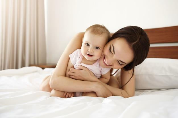 Glückliche schöne mutter in nachtwäsche, die auf bett mit ihrer kleinen tochter liegt, die lächelnd umarmt. Kostenlose Fotos