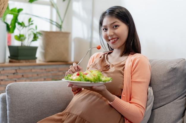 Glückliche schwangere asiatin, die gesundes lebensmittel des natürlichen gemüsesalats sitzt und isst und auf sofa sitzt Premium Fotos