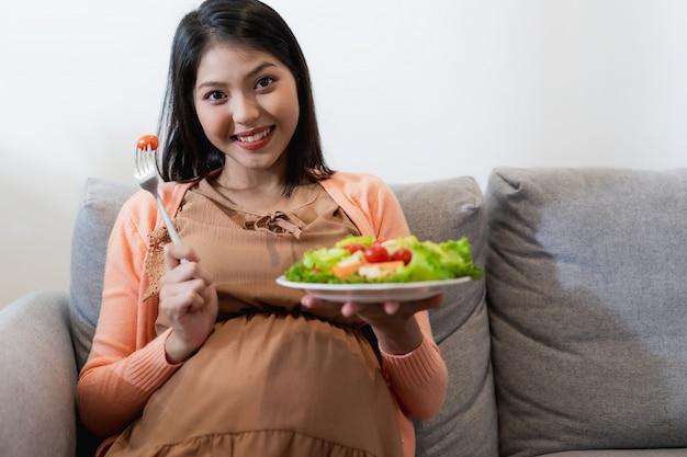 Glückliche schwangere asiatin, die natürlichen gemüsesalat, gesundes lebensmittel sitzt und isst und auf sofa sitzt Premium Fotos