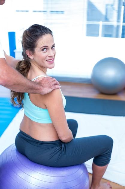 Glückliche schwangere frau, die entspannende massage an der turnhalle hat Premium Fotos