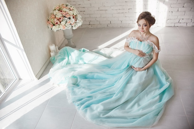 Glückliche schwangere frau im langen abendkleid Premium Fotos