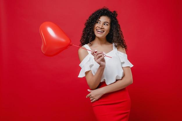 Glückliche schwarze frau mit herzen formte den tragenden rock des ballons, der auf roter wand lokalisiert wurde Premium Fotos