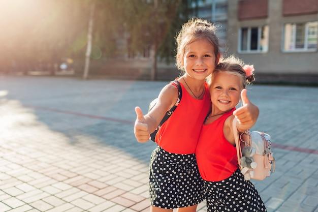 Glückliche schwestermädchen, die rucksäcke tragen und sich daumen zeigen. scherzt die schüler, die draußen schulgebäude lächeln. bildung Premium Fotos