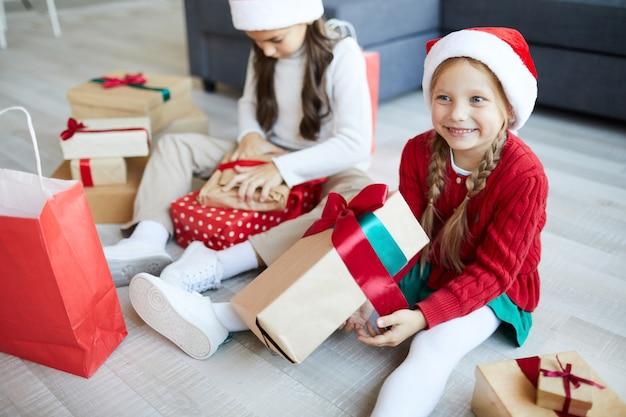 Glückliche schwestern, die weihnachtsgeschenke oder -geschenke auspacken Kostenlose Fotos