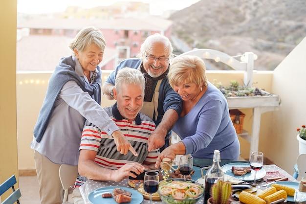 Glückliche senioren, die am intelligenten mobiltelefon am abendessen auf terrasse aufpassen Premium Fotos