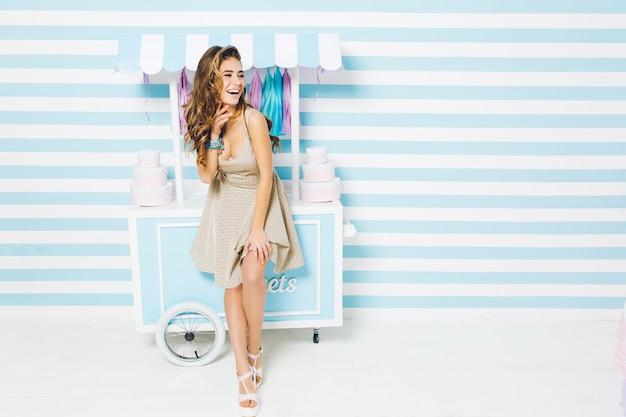 Glückliche sommerzeit des hübschen modischen modells im kleid, das spaß auf gestreifter wand hat. süßer dessert-truck, kuchen, lachen, wahre positive gefühle ausdrücken. Kostenlose Fotos