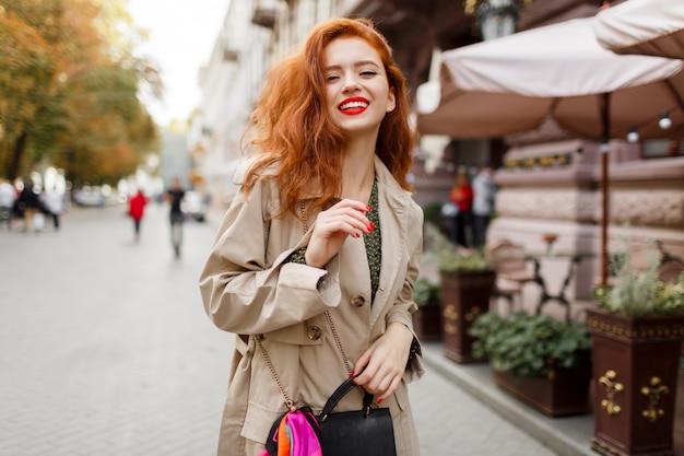 Glückliche sorglose frau mit roten haaren und hellem make-up, das auf der straße geht. beige mantel und grünes kleid tragen. Kostenlose Fotos