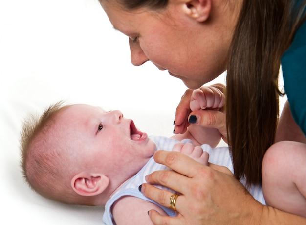 Glückliche spielende und lachende mutter und baby. Premium Fotos