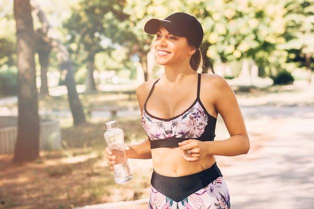 Glückliche sportliche junge frau, die plastikwasserflasche hält Kostenlose Fotos