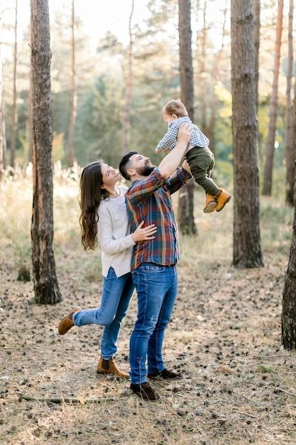 Glückliche stilvolle familie in freizeitkleidung, vater, mutter und kleiner sohn gehen im herbstwald spazieren, haben spaß und spielen mit dem baby Premium Fotos