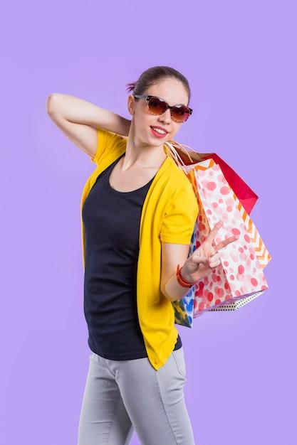Glückliche stilvolle frau, die friedenszeichen beim halten der schönen einkaufstasche zeigt Kostenlose Fotos