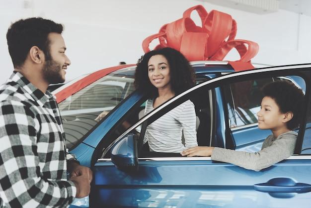 Glückliche stolze afro-frau erhielt neues luxuriöses auto Premium Fotos
