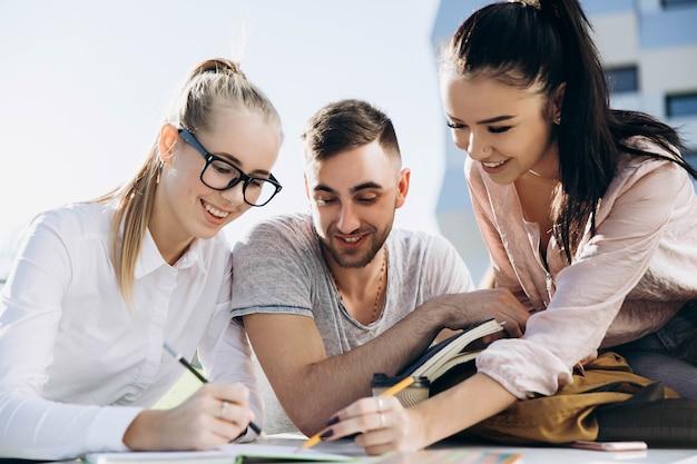 Glückliche studenten arbeiten und studieren am tisch an der frischen luft Premium Fotos