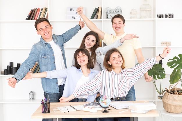 Glückliche studenten, die kamera betrachten Kostenlose Fotos