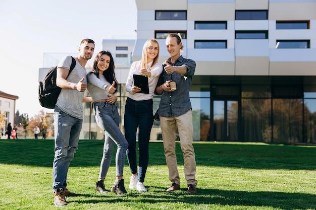 Glückliche studenten mit büchern gehen auf den grünen rasen vor der bibliothek Premium Fotos