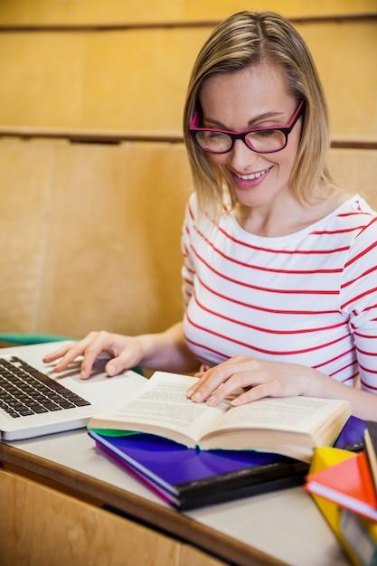Glückliche studentin, die laptop verwendet und an der universität liest Premium Fotos