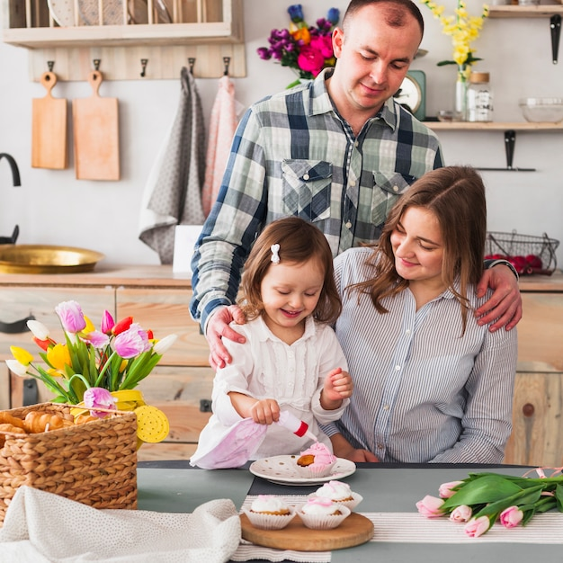 Glückliche tochter mit den eltern, die kleinen kuchen in der küche machen Kostenlose Fotos