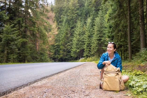 Glückliche touristin sitzt am straßenrand mit einem rucksack. outdoor-lifestyle-konzept für reisen und sommerferien Premium Fotos