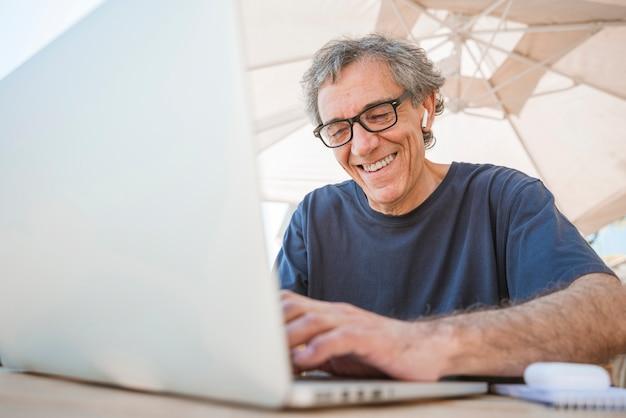 Glückliche tragende brillen des älteren mannes unter verwendung des laptops caf� im freien Kostenlose Fotos