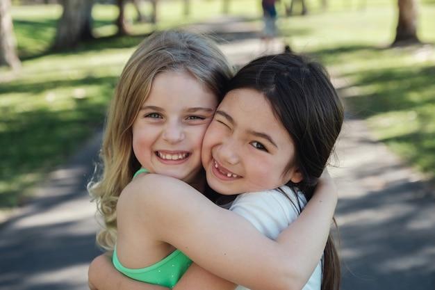 Glückliche und gesunde gemischte ethnische junge kleine mädchen, die im park, in den besten freunden und in der freundschaft umarmen und lächeln Premium Fotos