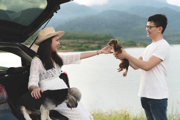 Glückliche und junge asiatische paare, die den lebensreiselebensstil mit haustieren genießen. Premium Fotos