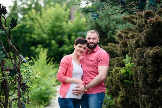 Glückliche und junge schwangere paare, die in der natur umarmen Premium Fotos