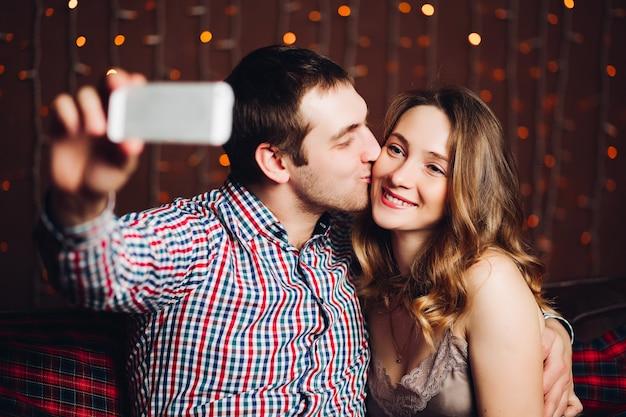 Glückliche und positive paare, die selbstporträt herein verziert für weihnachtsstudio machen. Premium Fotos