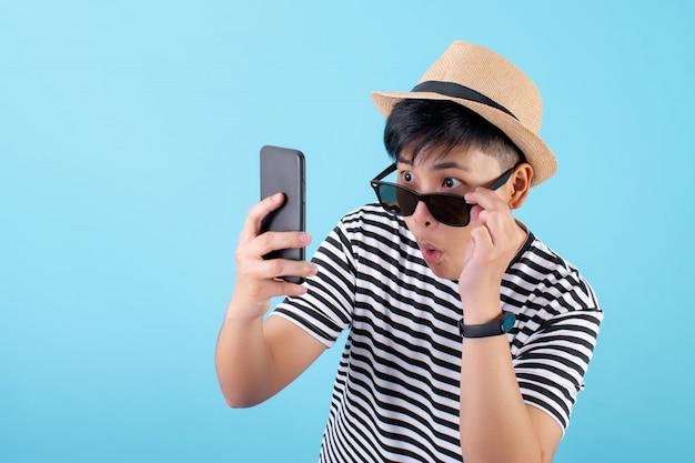 Glückliche und schockierte nachrichten des asiatischen touristen im smartphone auf einem blauen hintergrund Premium Fotos