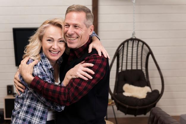 Glückliche und umarmte eltern, die zusammen aufwerfen Kostenlose Fotos
