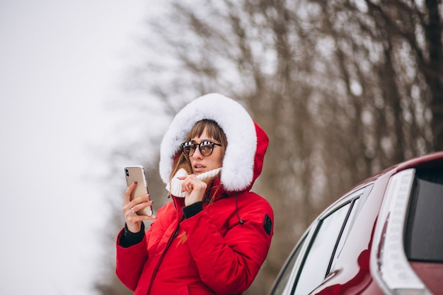 Glückliche unterhaltung der frau am telefon draußen mit dem auto im winter Kostenlose Fotos