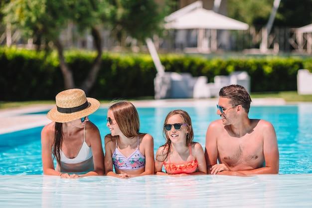 Glückliche vierköpfige familie am freienpool Premium Fotos