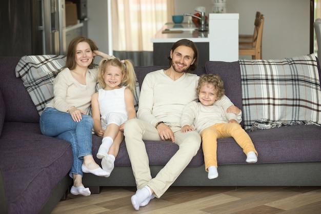 Glückliche vierköpfige familie, die auf dem sofa betrachtet kamera sitzt Kostenlose Fotos