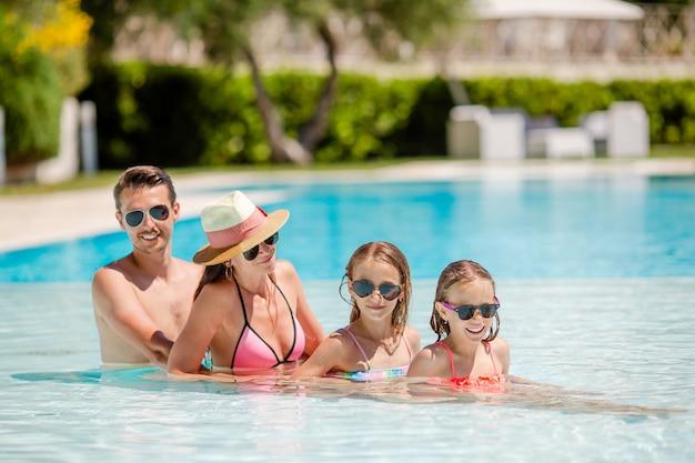 Glückliche vierköpfige familie im swimmingpool Premium Fotos