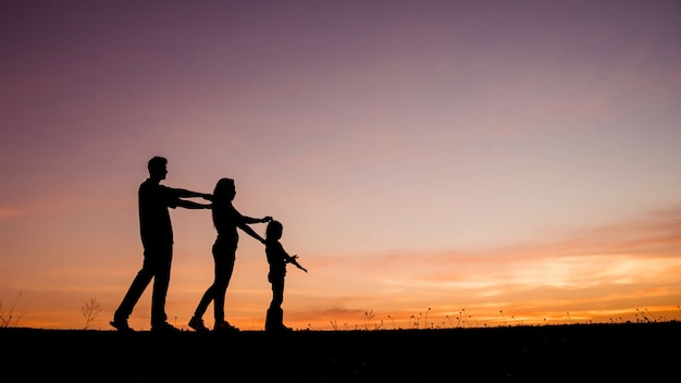 Glückliche vierköpfige familie, mutter, vater und tochter in der wiese. Premium Fotos