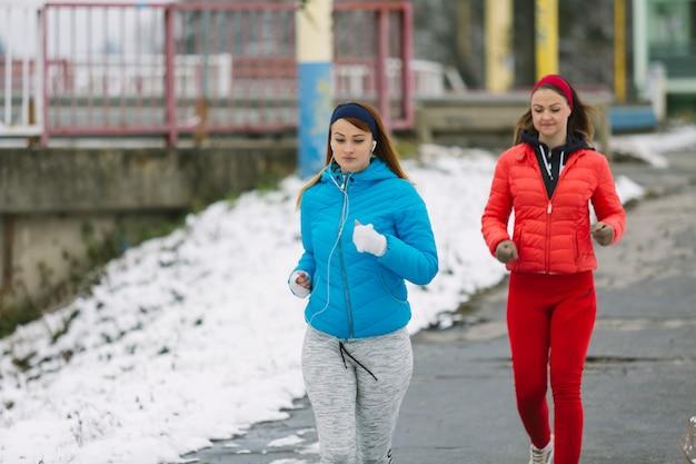 Glückliche weibliche athleten, die auf straße im winter laufen Kostenlose Fotos