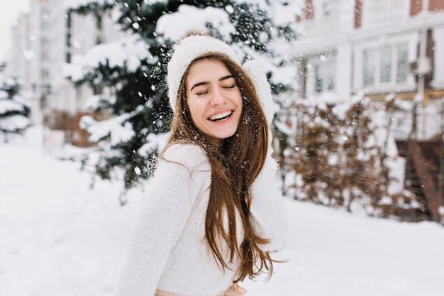 Glückliche wintermomente der freudigen jungen frau mit langen brünetten haaren, weiße winterkleidung, die spaß auf der straße in der schneezeit hat. positivität ausdrücken, wahre helle gefühle, mit geschlossenen augen lächeln. Kostenlose Fotos