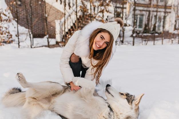 Glückliche winterzeit der erstaunlichen lächelnden frau, die mit dem heiseren hund im schnee spielt. charmante junge frau mit langen brünetten haaren, die spaß mit haustier auf straße voller schnee haben. helle wahre emotionen. Kostenlose Fotos