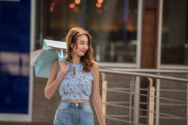 Glückliche zeit zum einkaufskonzept, asiatin, die einkaufstaschen in der mallmitte hält. Premium Fotos