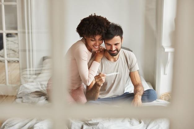 Glückliche zukünftige eltern gemischter rassen schauen freudig auf schwangerschaftstest, freuen sich über positive nachrichten über schwangerschaft, sitzen zusammen auf dem bett gegen häusliche innenräume. Kostenlose Fotos