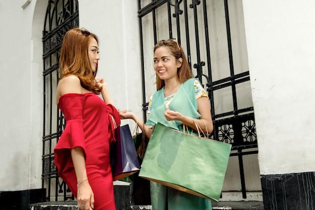 Glückliche zwei asiaten mit der einkaufstascheunterhaltung Premium Fotos