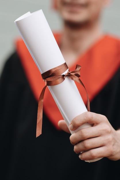 Glücklicher absolvent im kleid hält ein diplom des abschlusses Premium Fotos