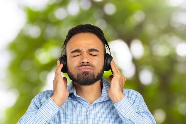 Glücklicher afrikanischer mann, der das hören musik in den kopfhörern lächelt Premium Fotos