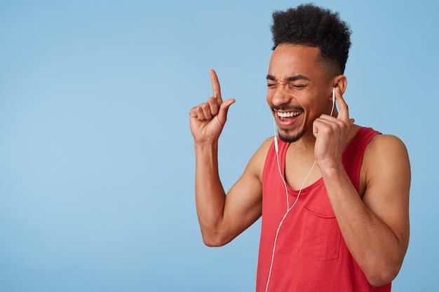 Glücklicher afroamerikaner attraktiver mann in einem roten trikot hört coole musik, hält ohrhörer mit der linken hand, schließt seine augen, singt und tanzt laut, steht auf. Kostenlose Fotos