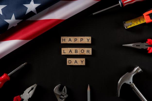 Glücklicher arbeitstag hölzerner text und amerikanische flagge auf dunkelheit Premium Fotos