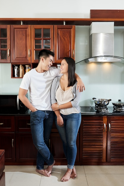 Glücklicher asiatischer freund und freundin, die einander in der küche umarmt und betrachtet Kostenlose Fotos