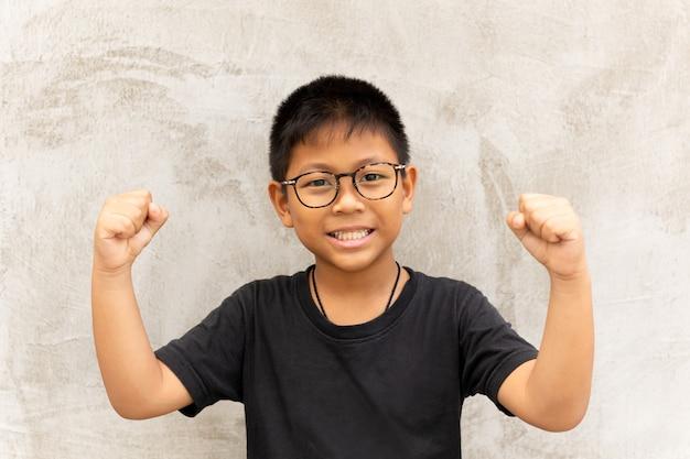 Glücklicher asiatischer junge mit gläsern übergibt oben und lächelt über grauem hintergrund. Premium Fotos