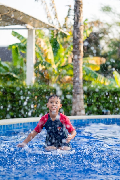 Glücklicher asiatischer kinderjunge, der auf swimmingpool im sommer schwimmt Premium Fotos