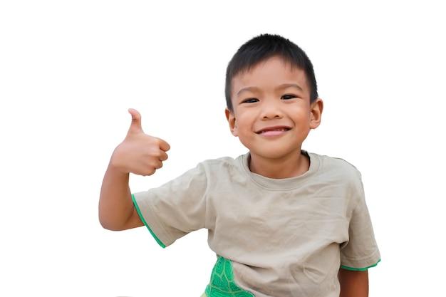 Glücklicher asiatischer kinderjunge, der daumen oben zeigt. auf einem weißen hintergrund. Premium Fotos
